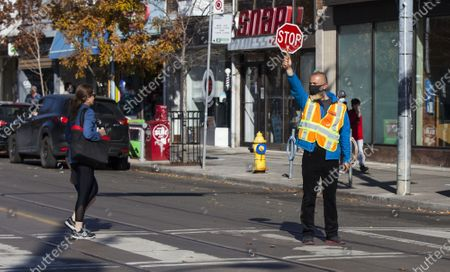A crossing guard wearing a face mask works on a street in Toronto, Canada, on Nov. 10, 2020. Canadian Prime Minister Justin Trudeau called on local governments Tuesday to do the right thing to stem record-breaking spikes of new COVID-19 cases across the country. As of Tuesday afternoon, Canada reported a total of 272,512 cases of the COVID-19 and 10,629 deaths, according to CTV.