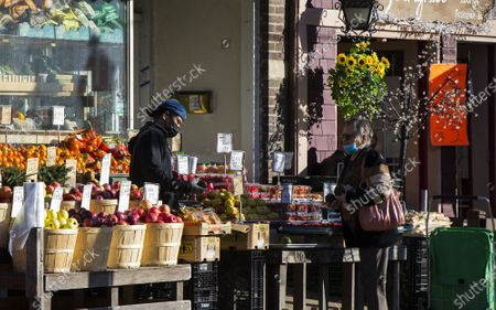 A shop assistant wearing a face mask picks up a fruit for a customer at a stall in Toronto, Canada, on Nov. 10, 2020. Canadian Prime Minister Justin Trudeau called on local governments Tuesday to do the right thing to stem record-breaking spikes of new COVID-19 cases across the country. As of Tuesday afternoon, Canada reported a total of 272,512 cases of the COVID-19 and 10,629 deaths, according to CTV.