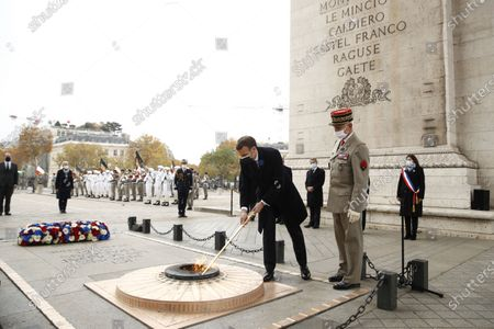 French President Emmanuel Macron (L) lights up the flame at the tomb of the unknown soldier next to French Armies Chief of Staff General Francois Lecointre (R) during a ceremony at the Arc de Triomphe in Paris, France, 11 November 2020, as part of the commemorations marking the 102nd anniversary of the 11 November 1918 armistice, ending World War I (WWI).