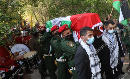 Palestinian honor guard and the two sons of late Palestinian politician and diplomat Saeb Erekat carry his coffin during funeral in the West Bank city of Jericho, 11 November 2020. Erekat, the chief Palestinian negotiator, died on 10 November after contracting the coronavirus disease (COVID-19).