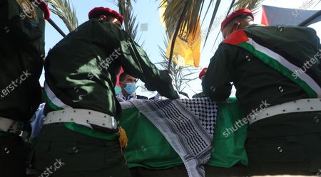 Palestinian honor guard carry the coffin of late Palestinian politician and diplomat Saeb Erekat, during his funeral in the West Bank city of Jericho, 11 November 2020. Erekat, the chief Palestinian negotiator, died on 10 November after contracting the coronavirus disease (COVID-19).
