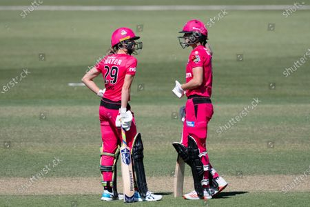 Stock Picture of Erin Burns and Ellyse Perry of the Sydney Sixers between overs during the Women's Big Bash League cricket match between Perth Scorchers and Sydney Sixers