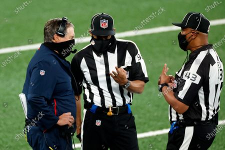 New England Patriots head coach Bill Belichick talks with field judge Terry Brown (43) and head linesman Greg Bradley (98) during an NFL football game against the New York Jets, in East Rutherford, N.J