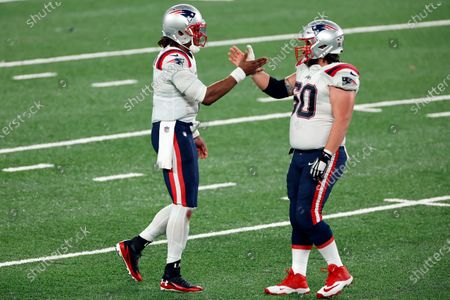 New England Patriots quarterback Cam Newton (1) reacts with New England Patriots center David Andrews (60) during an NFL football game against the New York Jets, in East Rutherford, N.J