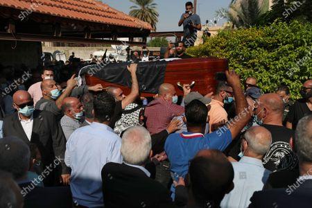 Mourners carry the body Saeb Erekat into the family house during his funeral in the West Bank city of Jericho, . Erekat, a veteran peace negotiator and prominent international spokesman for the Palestinians for more than three decades, died on Tuesday, weeks after being infected by the coronavirus. He was 65