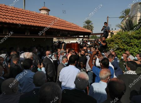Stock Image of Mourners carry the body Saeb Erekat into the family house during his funeral in the West Bank city of Jericho, . Erekat, a veteran peace negotiator and prominent international spokesman for the Palestinians for more than three decades, died on Tuesday, weeks after being infected by the coronavirus. He was 65