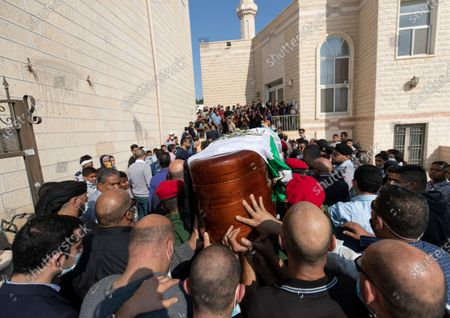 Palestinian honor guard carries the body Saeb Erekat into a mosque during his funeral in the West Bank city of Jericho, . Erekat, a veteran peace negotiator and prominent international spokesman for the Palestinians for more than three decades, died on Tuesday, weeks after being infected by the coronavirus. He was 65