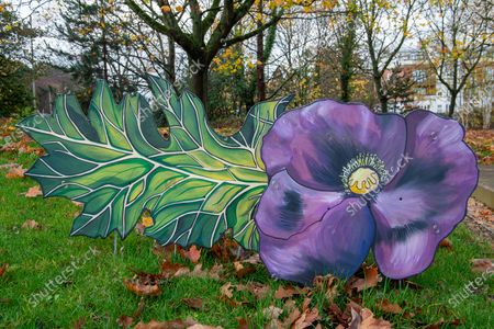 Stock Image of A meadow of painted purple poppies by artist Jenna Fox have been left by the bronze scuplture of the War Horse Memorial in Ascot to mark Remembrance Sunday and Armistice Day 2020. Millions of horses, mules and donkey perished in the Great War. The bronze horse scuplture by Susan Leyland named Poppy, has a tear trickling from the horse's eye. People across the country will fall silent for two minutes at 11.00am on 11th November 2020 as they pay their respects to the war dead of World War I, World War II and more recent conflicts across the world