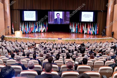 This photo released by the Syrian official news agency SANA, shows Syrian President Bashar Assad virtually addressing the opening session of a two-day international conference on the return of refugees to Syria, organized by Russia, in Damascus, Syria, . The Syrian government is working to secure the return of millions of refugees who fled war in their country, but Western sanctions are hindering the work of state institutions, complicating those plans, Assad said Wednesday