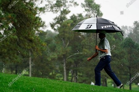 Fred Couples walks in the rain along the fourth fairway during a practice round for the Masters golf tournament, in Augusta, Ga