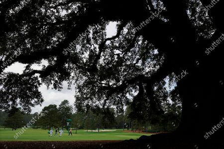 Graeme McDowell, of Northern Ireland, and Shane Lowry, of Ireland, walk down the 18th fairway during a practice round for the Masters golf tournament, in Augusta, Ga