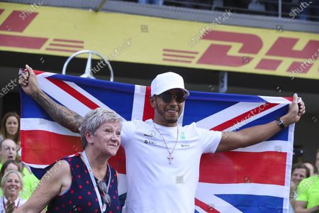 Stock Picture of Autodromo Hermanos Rodriguez, Mexico City, Mexico. Sunday 29 October 2017. Lewis Hamilton, Mercedes AMG, celebrates with his mum Carmen Larbalestier, his team and a Union flag across his shoulders, after securing his 4th world drivers championship title, and third with Mercedes. World Copyright: Charles Coates/LAT Images