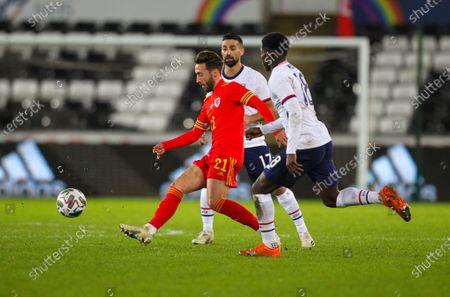 Josh Sheehan of Wales passes the ball while under pressure from Sebastian Lletget and Yunus Musah of USA; Liberty Stadium, Swansea, Glamorgan, Wales; International Football Friendly; Wales versus United States of America.
