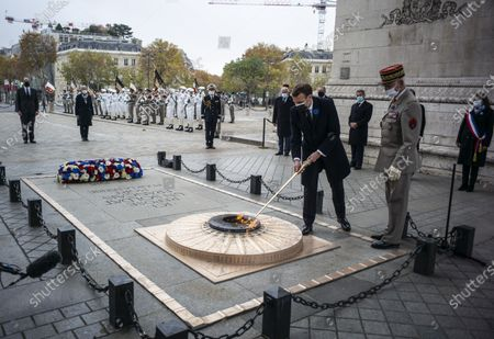 French President Emmanuel Macron (L) lights up the flame at the tomb of the unknown soldier next to French Armies Chief of Staff General Francois Lecointre (R) during a ceremony at the Arc de Triomphe in Paris