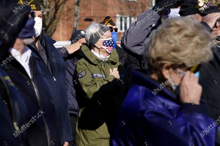 Stock Picture of Collette McGrath, center, and veterans salute during a Veterans Day ceremony at the Veterans Memorial Waterfall in Niles, Ill., . Collette McGrath attends the ceremony instead of her husband Thomas McGrath who is a veteran of Foreign War