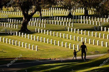 """Stock Photo of Army veteran Christian Cohuo, who served in South Korea brought his Grandson, Mateo Sandoval, 3, to honor Veterans Day at Los Angeles National Cemetery. """"Some people I served with are buried here and I want to make this a tradition,"""" Christian said. Los Angeles National Cemetery on Wednesday, Nov. 11, 2020 in Los Angeles, CA. (Al Seib / Los Angeles Times"""