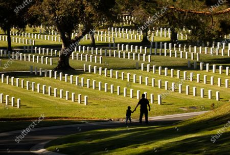 """Army veteran Christian Cohuo, who served in South Korea brought his Grandson, Mateo Sandoval, 3, to honor Veterans Day at Los Angeles National Cemetery. """"Some people I served with are buried here and I want to make this a tradition,"""" Christian said. Los Angeles National Cemetery on Wednesday, Nov. 11, 2020 in Los Angeles, CA. (Al Seib / Los Angeles Times"""
