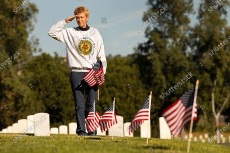 """Saluting female veterans, Julie Robinson, 56, a veteran who served in the Air Force as a Environmental Support Specialist in the 1980's brought over 100 flags to place on Veterans grave markers to honor Veterans Day at Los Angeles National Cemetery. Julie's former husband who was also a veteran is buried at the Sacramento Valley National Cemetery. """"It's my way to honor my fellow veterans. Somebody needs to do it."""" She said. Los Angeles National Cemetery on Wednesday, Nov. 11, 2020 in Los Angeles, CA. (Al Seib / Los Angeles Times"""