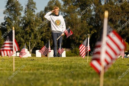 """Stock Picture of Saluting female veterans, Julie Robinson, 56, a veteran who served in the Air Force as a Environmental Support Specialist in the 1980's brought over 100 flags to place on Veterans grave markers to honor Veterans Day at Los Angeles National Cemetery. Julie's former husband who was also a veteran is buried at the Sacramento Valley National Cemetery. """"It's my way to honor my fellow veterans. Somebody needs to do it."""" She said. Los Angeles National Cemetery on Wednesday, Nov. 11, 2020 in Los Angeles, CA. (Al Seib / Los Angeles Times"""