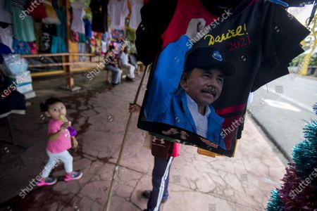 A girl (L) walks through a mobile t-shirt shop with the image of Nicaraguan President Daniel Ortega in Managua, Nicaragua, 11 November 2020. The president of Nicaragua, Daniel Ortega, turns 75 this Wednesday, without showing signs of wanting to leave power, after almost 14 consecutive years of mandate.