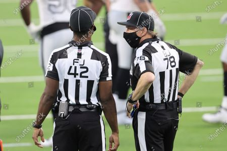Back judge Greg Meyer (78) and referee Jeff Triplette (42) chat during stoppage time during an NFL football game between the Las Vegas Raiders and the Los Angeles Chargers, in Inglewood, Calif