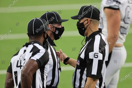 Head linesman Jerod Phillips (6) and referee Jeff Triplette (42), and back judge Greg Meyer (78) discuss a call during an NFL football game between the Las Vegas Raiders and the Los Angeles Chargers, in Inglewood, Calif