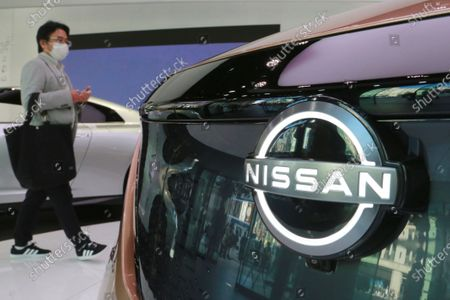 Visitor walks past a car at Nissan Motor Co.'s showroom in Tokyo, . Nissan posted a loss of 44.4 billion ($421 million) for the fiscal second quarter, as the coronavirus pandemic slammed profitability, and the Japanese automaker fought to restore brand image tarnished by the scandal of its former star executive Carlos Ghosn, reported Thursday, Nov. 12, 2020