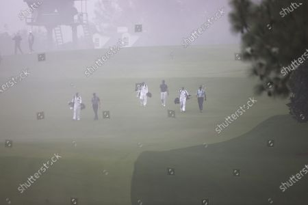 Stock Image of The first group of Sandy Lyle from Scotland, Yuxin Lin of China and Jimmy Walker of the US walks down the fairway in the fog on the tenth hole during the first round of the 2020 Masters Tournament at the Augusta National Golf Club in Augusta, Georgia, USA, 12 November 2020. After being delayed seven months by the coronavirus pandemic, the 2020 Masters Tournament is being held without patrons 12 November through 15 November.