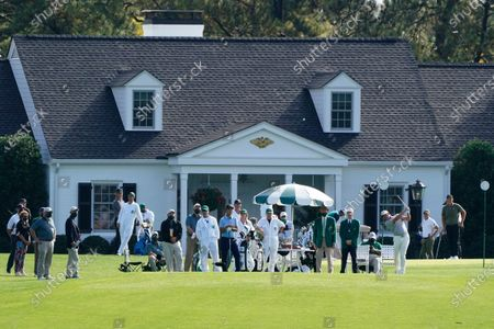 Watched by a sparse contingent, Lee Westwood, far right, of England, tees off on the first hole during the first round of the Masters golf tournament, in Augusta, Ga