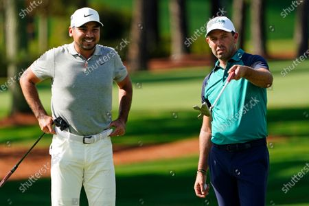 Jason Day, left, of Australia, and Charl Schwartzel, of South Africa, wait to putt on the second hole during the first round of the Masters golf tournament, in Augusta, Ga
