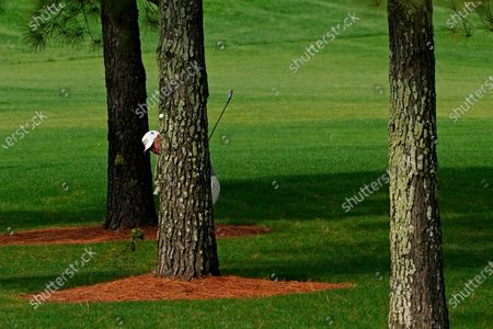 Lee Westwood, of England, hits from behind a tree on the seventh hole during the first round of the Masters golf tournament, in Augusta, Ga