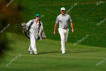 Lee Westwood, of England, talks to his caddie Helen Storey on the seventh hole during the first round of the Masters golf tournament, in Augusta, Ga