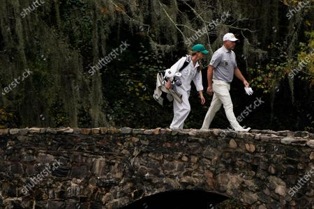 Lee Westwood, of England, walks with his caddie Helen Storey on the 13th hole during the first round of the Masters golf tournament, in Augusta, Ga
