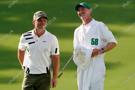 Paul Casey, of England, laughs with his caddie John MacLaren after his first round of the Masters golf tournament, in Augusta, Ga
