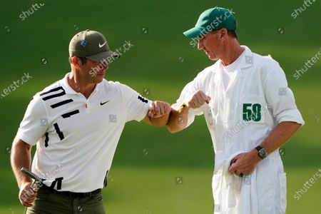 Paul Casey, of England, touches elbows with his caddie John MacLaren after his first round of the Masters golf tournament, in Augusta, Ga
