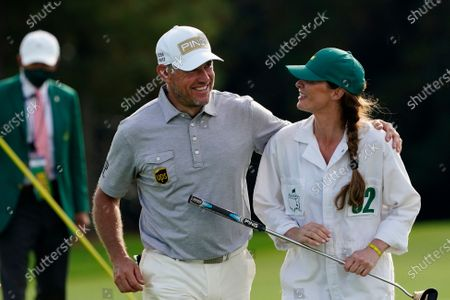 Lee Westwood, of England, walks off the ninth hole with his caddie Helen Storey following his first round of the Masters golf tournament, in Augusta, Ga