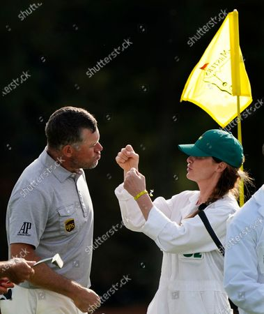 Lee Westwood, of England, waits for a kiss from his caddie Helen Storey following his first round of the Masters golf tournament, in Augusta, Ga