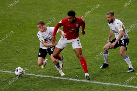 Daniel Powell of Crewe Alexandra competes with Louis Reed and Dan Butler of Peterborough United