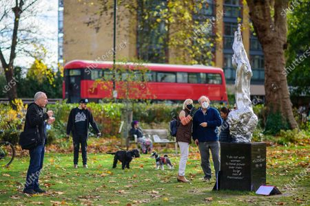Stock Photo of Visitors at the controversial Mary Wollstonecraft sculpture by Maggi Hambling on Newington Green