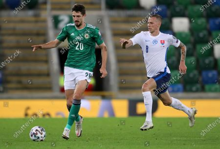Northern Ireland's Craig Cathcart, left, and Slovakia's Ondrej Duda battle for the ball during the Euro 2020 playoff semifinal soccer match between Northern Ireland and Slovakia at Windsor Park, Belfast, Northern Ireland