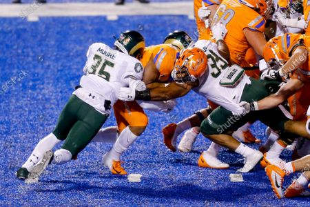 Colorado State defensive lineman Manny Jones (33) and linebacker Aaron Moore (35) stop Boise State running back Andrew Van Buren (21) behind the line of scrimmage during the first half of an NCAA college football game, in Boise, Idaho