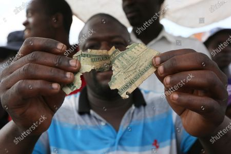 Albert Marombe holds up a a grimmy, tattered $20 bill at a busy market in Harare, in this photo. Worn out or shredded by rats, one dollar notes are king in Zimbabwe, beset by a continuing economic crisis, and enterprising traders are repairing old notes for desperate customers