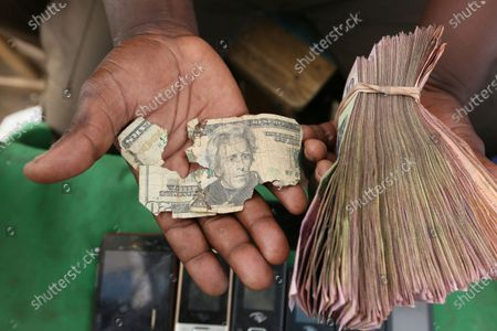 Stock Picture of Albert Marombe holds a grimmy, tattered $20 bill at a busy market in Harare, in this photo. Worn out or shredded by rats, one dollar notes are king in Zimbabwe, beset by a continuing economic crisis, and enterprising traders are repairing old notes for desperate customers