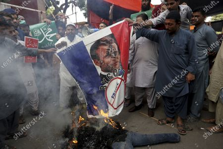 Supporters of Jamaat-e-Islami, a religious political party, burns a representation of a French flag with a defaced image of French President Emmanuel Macron during a protest against the French president and republishing of caricatures of the Prophet Muhammad they deem blasphemous, in Karachi, Pakistan