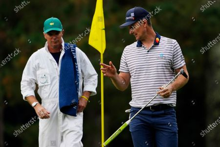Justin Rose, of England, speaks to his caddie Gareth Bryn Lord after putting on the 14th hole during the first round of the Masters golf tournament, in Augusta, Ga