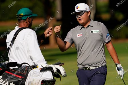 Sungjae Im, of South Korea, fist bumps his caddie Robert Gregory Brown after a birdie on the 15th hole during the second round of the Masters golf tournament, in Augusta, Ga