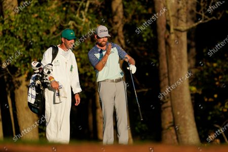 Webb Simpson discusses his shot that went into the water on the 11th hole with his caddie Paul Tesori during the second round of the Masters golf tournament, in Augusta, Ga