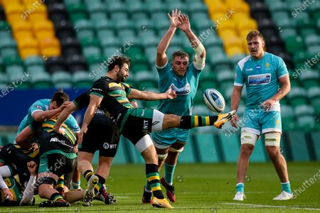 Tom Dodd of Worcester Warriors charges down a kick from Henry Taylor of Northampton Saints