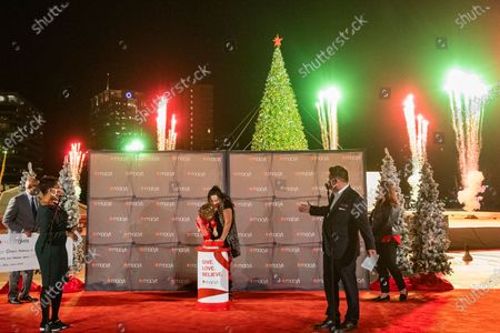 Macy's Lenox Square Store Manager Brian Williams, right, Children's Healthcare of Atlanta 3-year-old Patient Kenni, and Atlanta Mayor Keisha Lance Bottoms, left, light this year's Macy's Great Tree at a private ceremony, in Atlanta