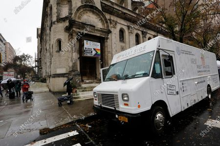 People queue up to receive food from the West Side Campaign Against Hunger at St. Paul & St. Andrew United Methodist Church on West 86th Street in New York, New York, USA, 13 November 2020.